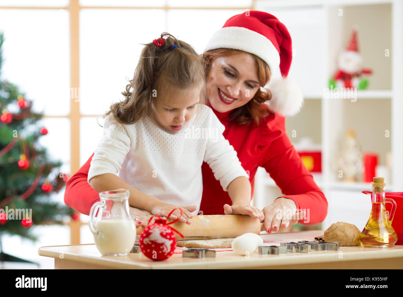 family mother and child rolling the dough, bake christmas cookies in festival decorated room - Stock Image
