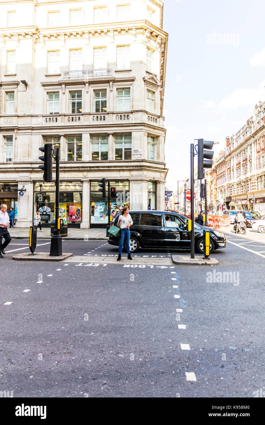 Crossing road in London, Crossing road with shopping bags, carrying shopping bags, designer shopping bags, waiting - Stock Image