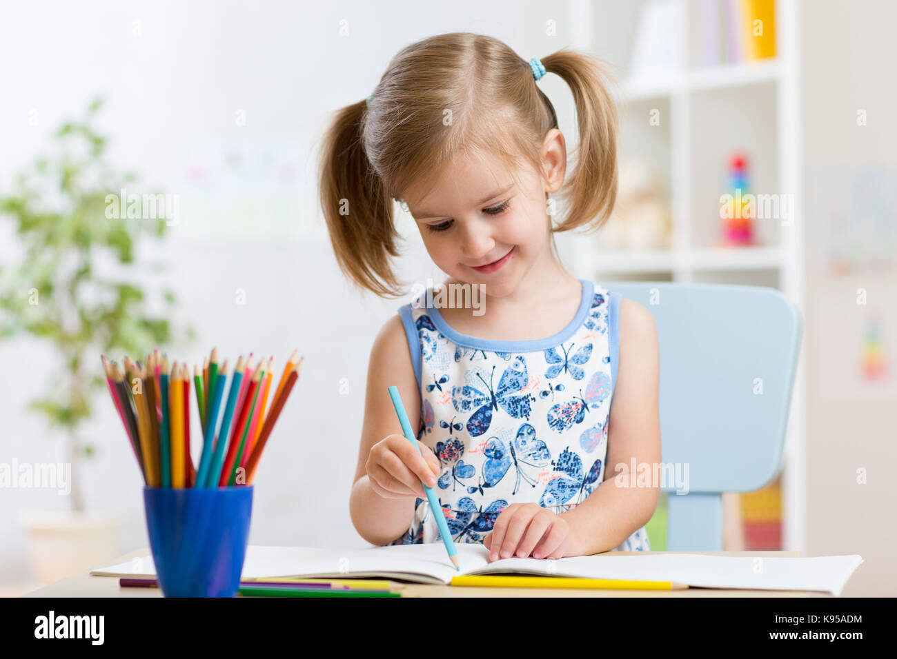 Child girl drawing with colorful pencils in nursery - Stock Image
