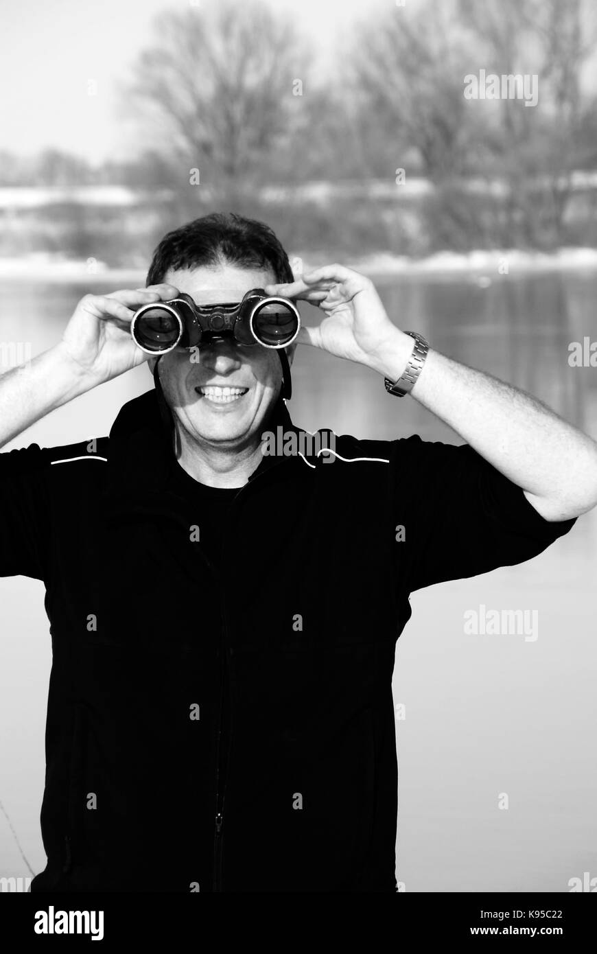 Man looking in the distance with binoculars - Stock Image