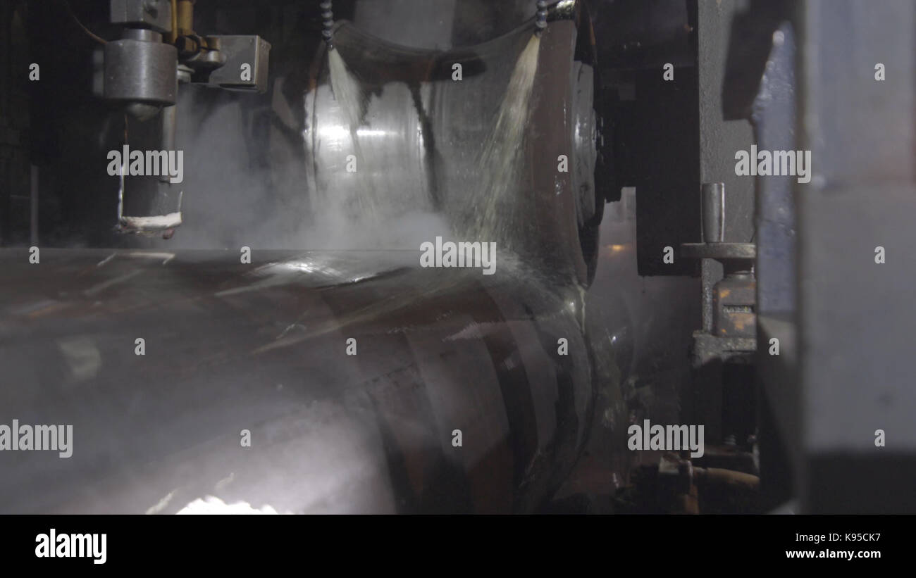 Tube rolling process at manufacturing plant. Closeup of production process of metal pipe. Industrial machinery in - Stock Image
