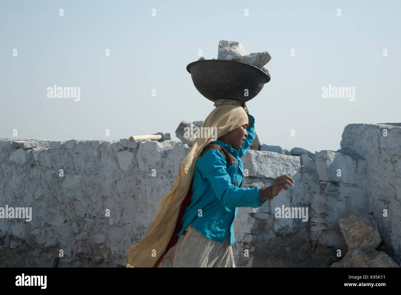 girls working in at the lime kilns, carrying blocks of limestone over to the kilns - Stock Image