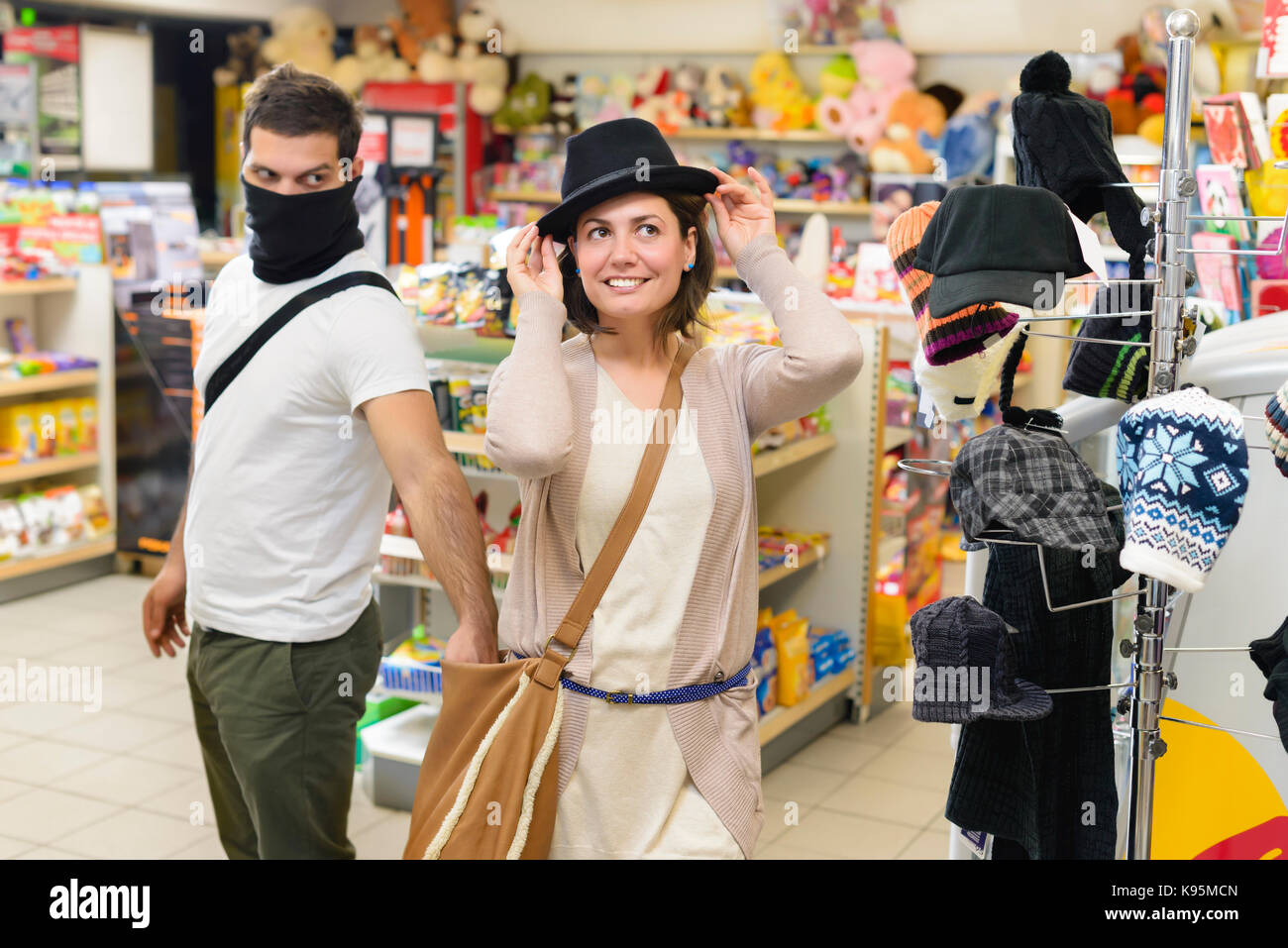 Thief stealing from handbag of a woman trying a hat  in a store - Stock Image