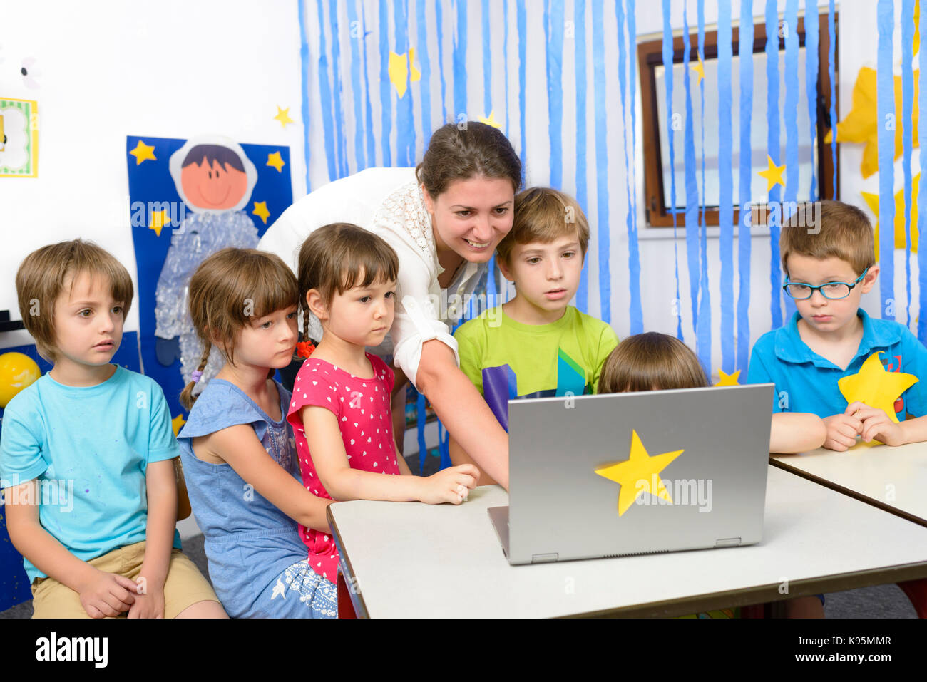 Educator surrounded by  kids at kindergarten using a laptop - Stock Image