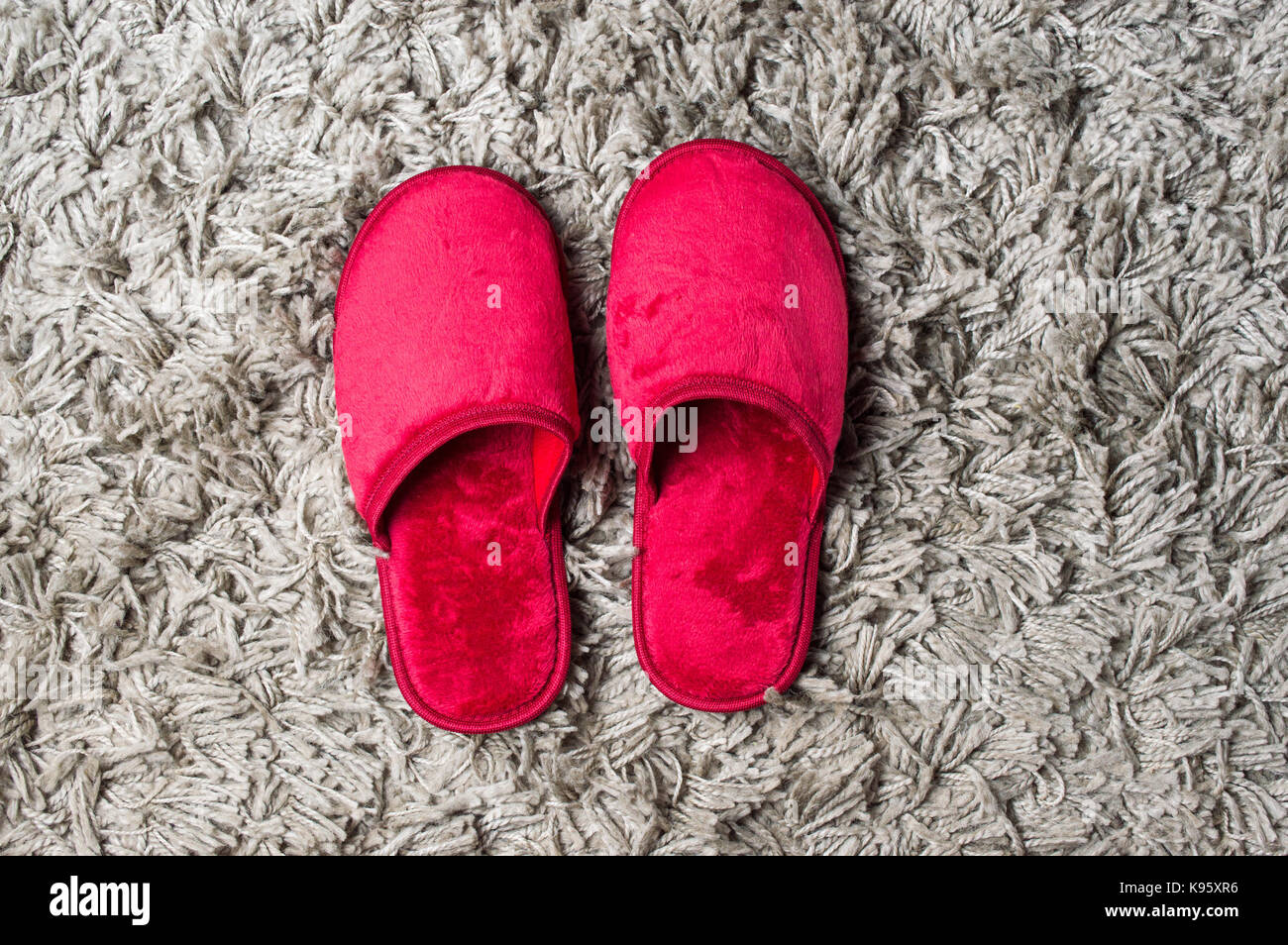 73536191897 Red house slippers on fluffy gray carpet Stock Photo  160556010 - Alamy