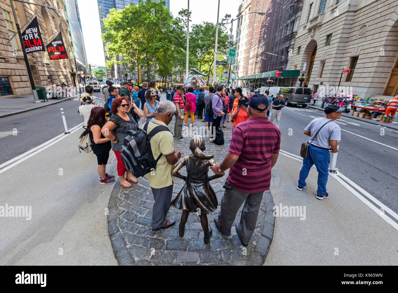 The Charging Bull Statue and the Fearless Girl Statue surrounded by tourists in the Financial District, near the - Stock Image