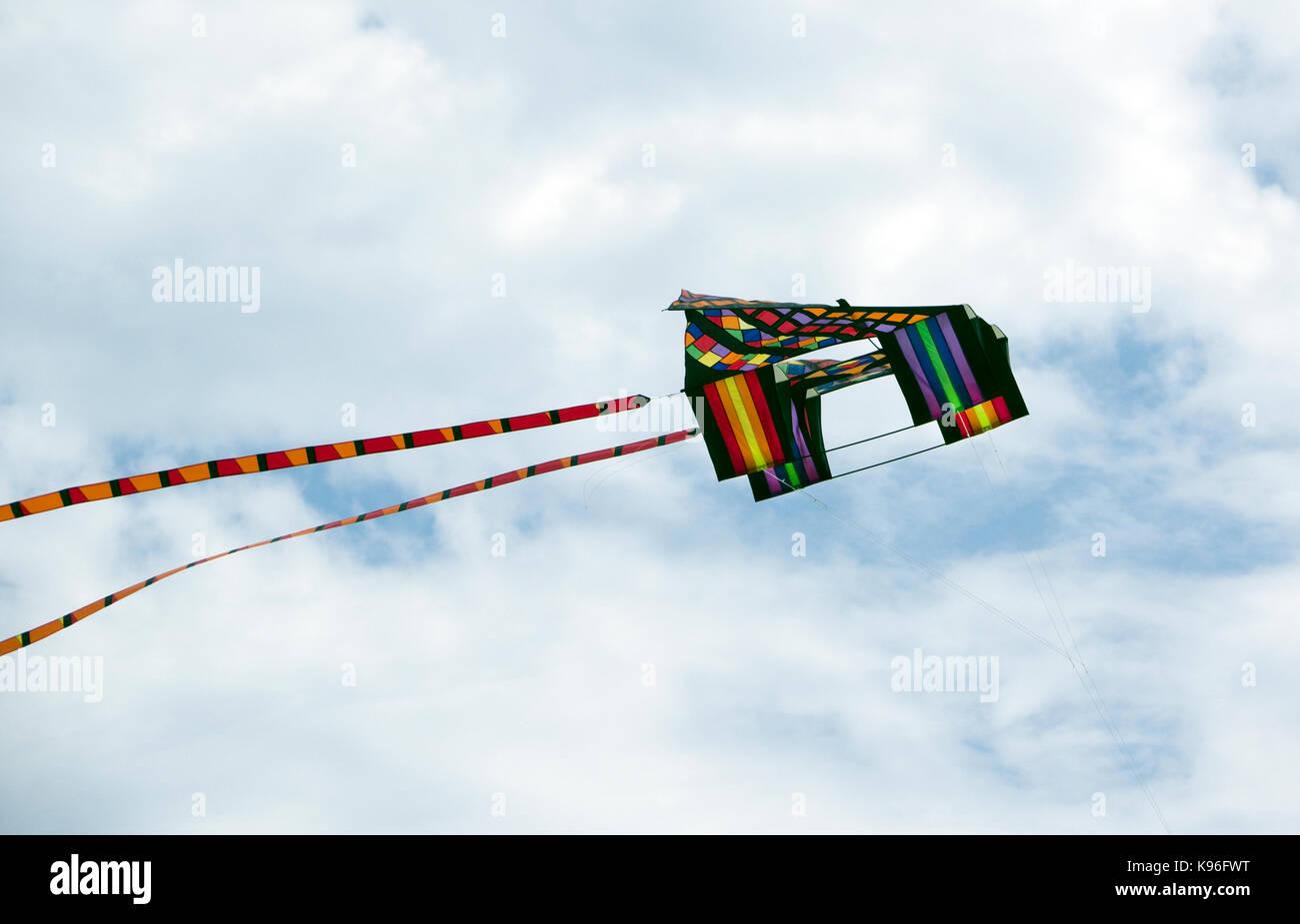 Colorful box kite in flight over  Neshotah Beach Two Rivers, Wisconsin during Kites Over Lake Michigan annual kite - Stock Image