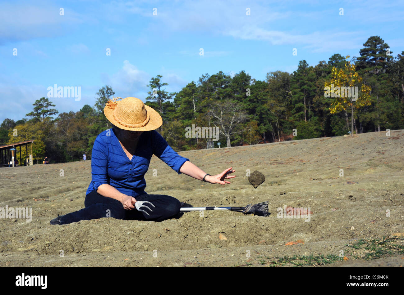 Woman, wearing a straw hat, sits in the diamond field at Crater of Diamonds State Park in Murfreesboro, Arkansas. - Stock Image