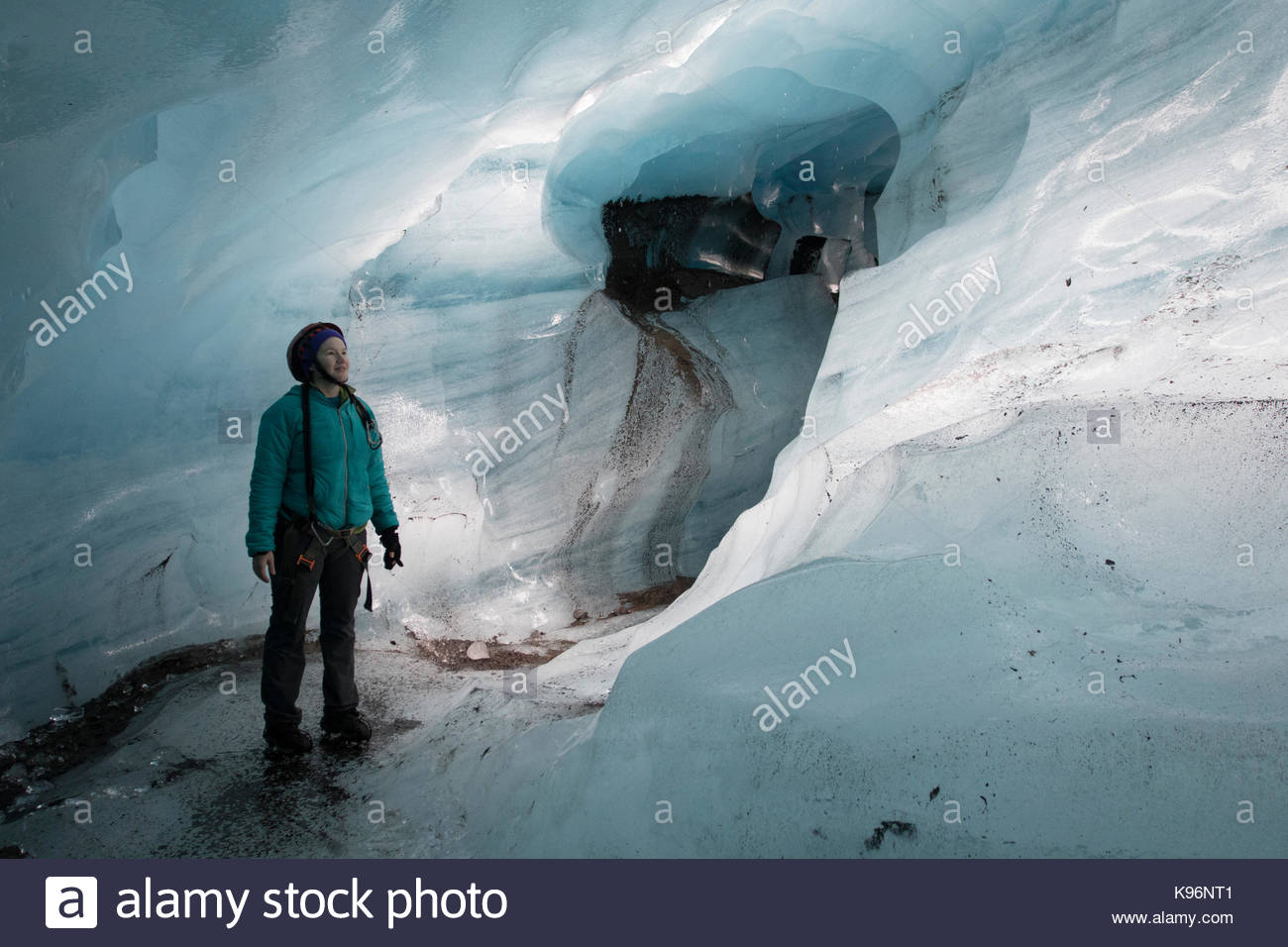 A woman stands in a natural ice cave that formed under Svinafellsjokull. - Stock Image