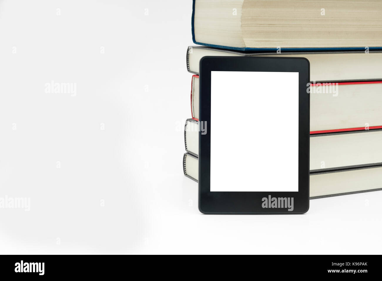 E-book device with books in white isolated background. - Stock Image