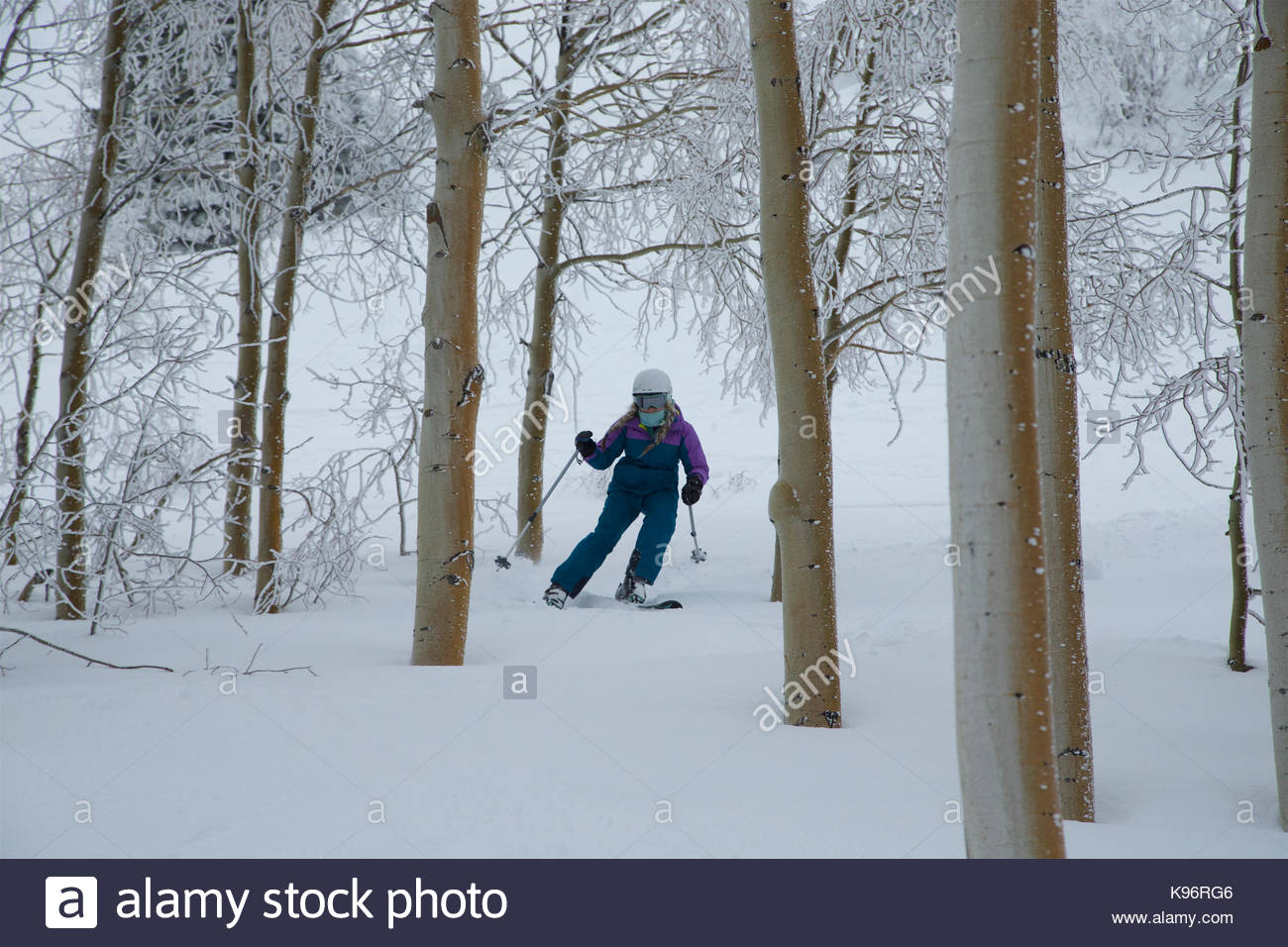 A teen girl downhill skiing through the trees on a stormy day. - Stock Image