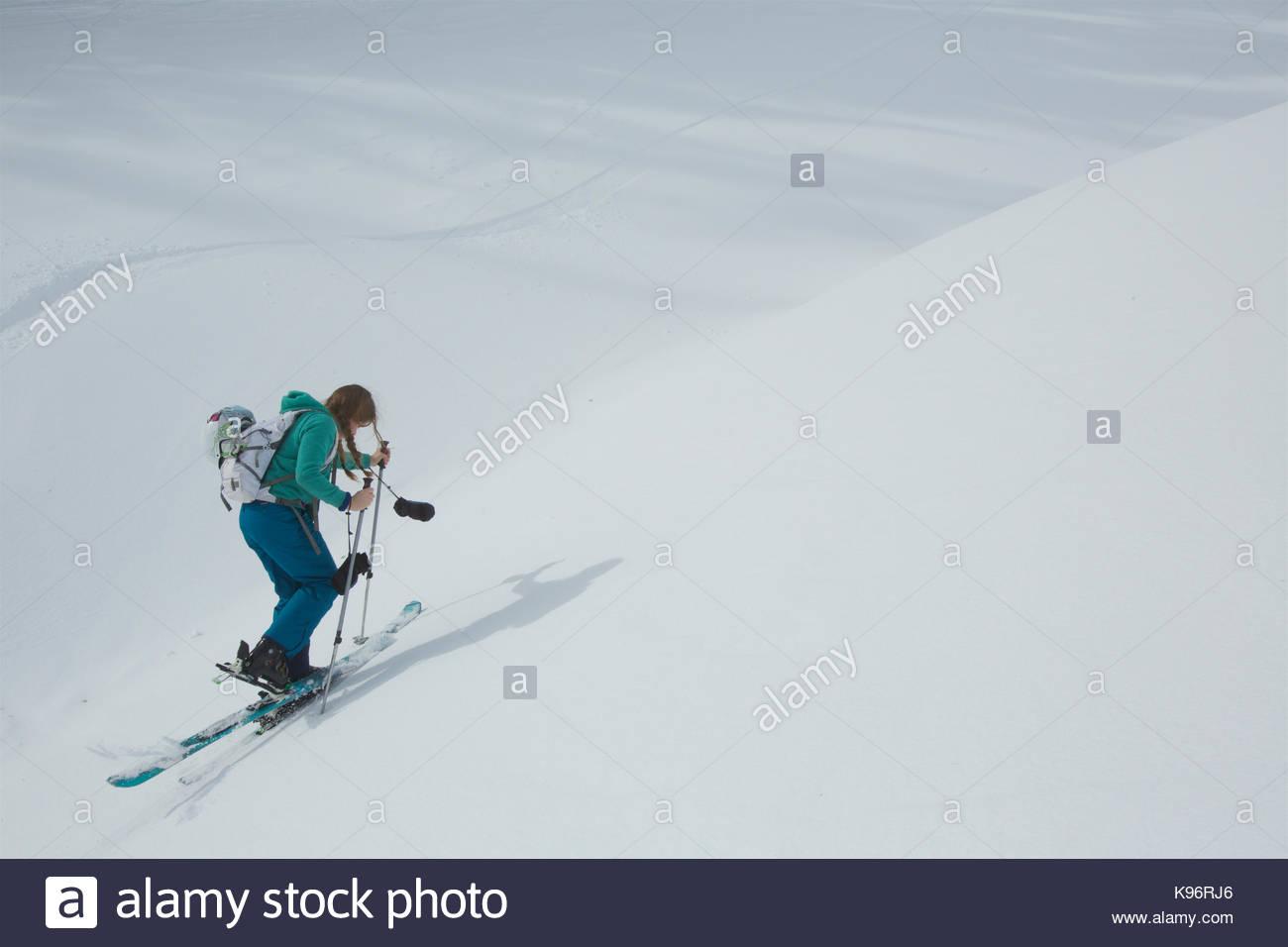 Teen girl skiing uphill with skins on her skis. - Stock Image