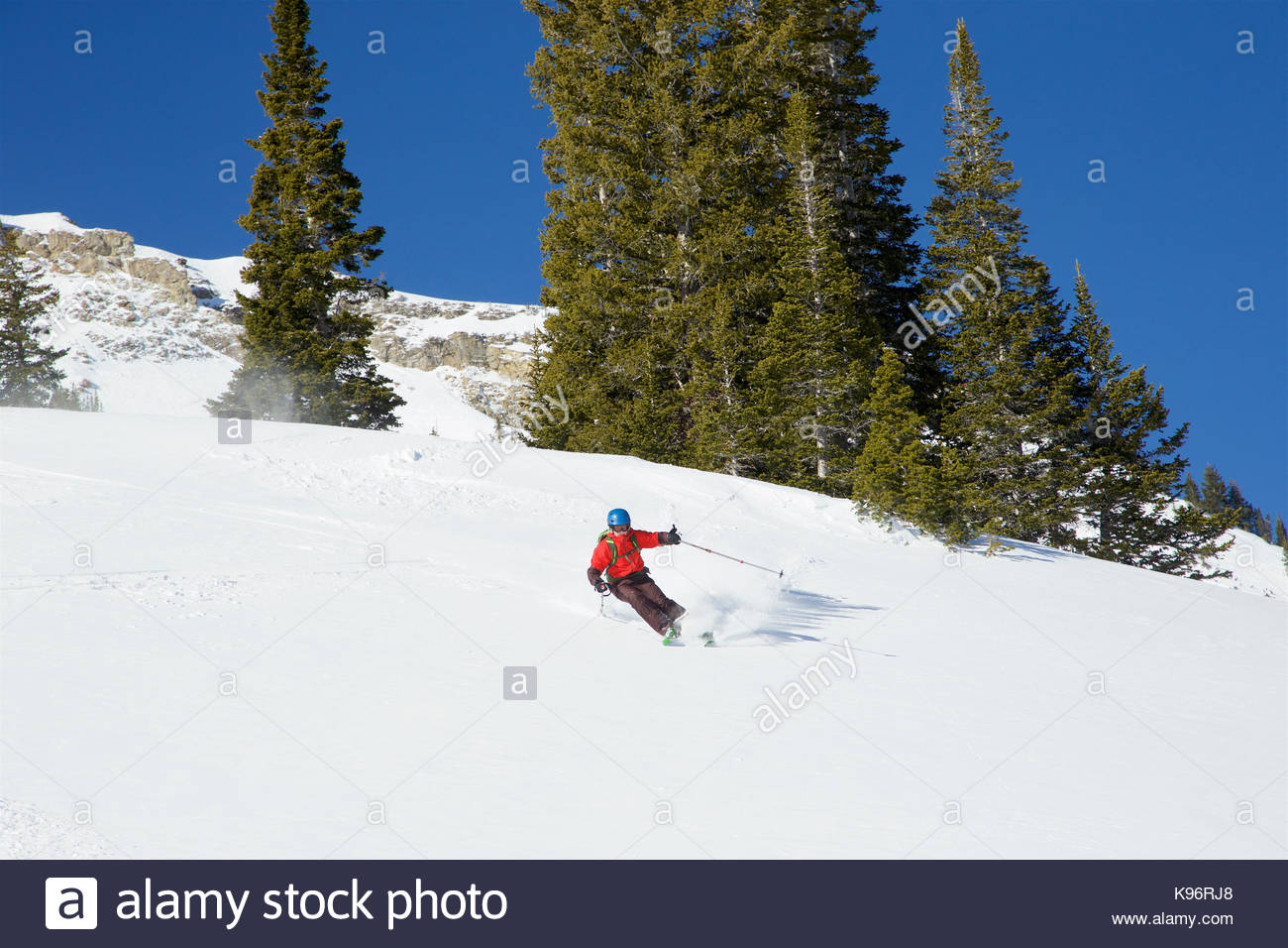 A teen boy skiing fresh powder on a sunny day after a storm. Stock Photo