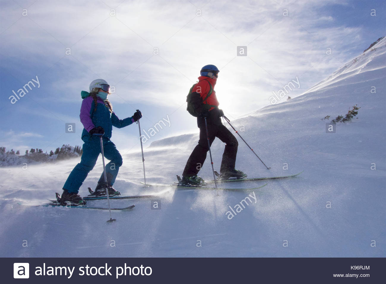 Teen siblings skiing across the top of a mountain on a sunny day. - Stock Image