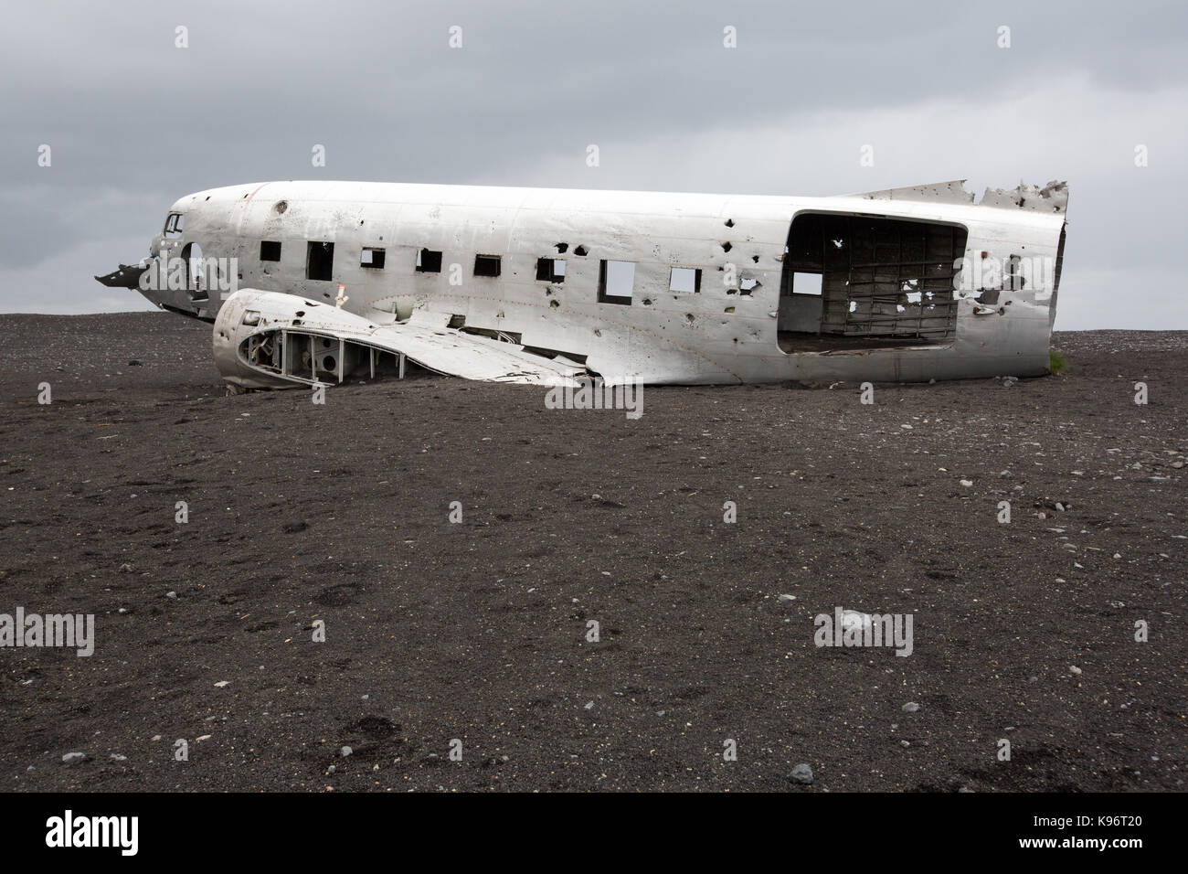 An abandoned United States Navy plane crashed and rests in black sand. - Stock Image