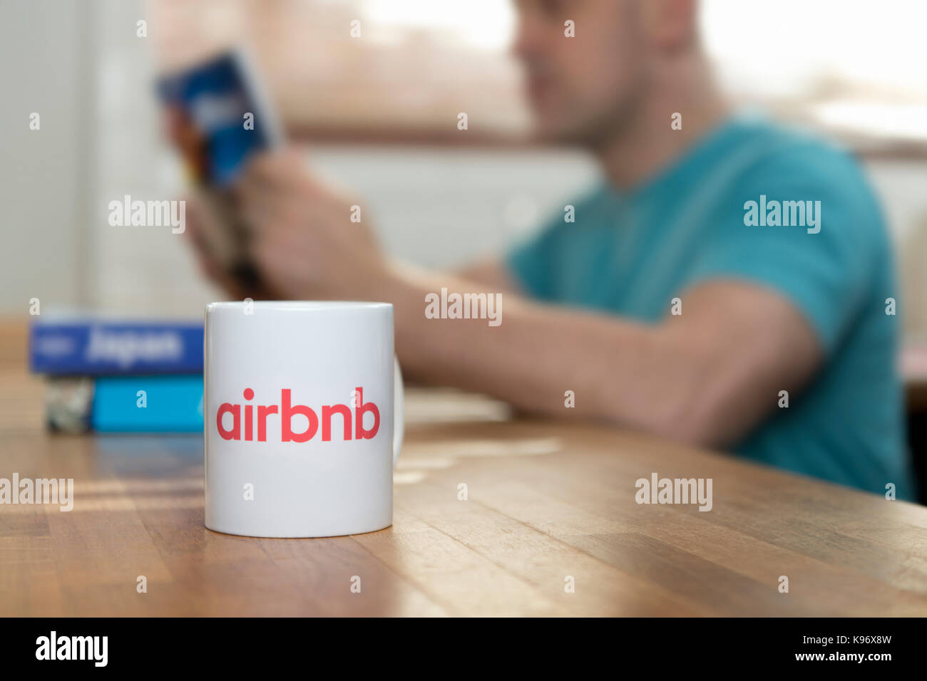A man reads travel guide books in a flat he has rented using the Airbnb app, and a branded Airbnb mug sits in the Stock Photo