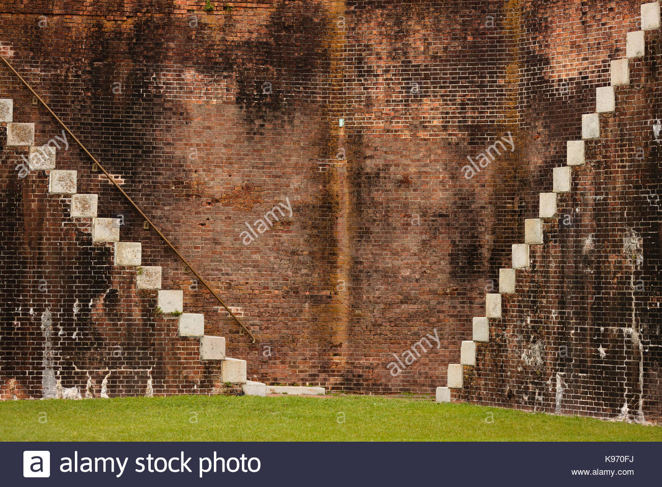 Looking at the side view of two very steep stairs inside Fort Morgan, Alabama, that come down from the top of the - Stock Image