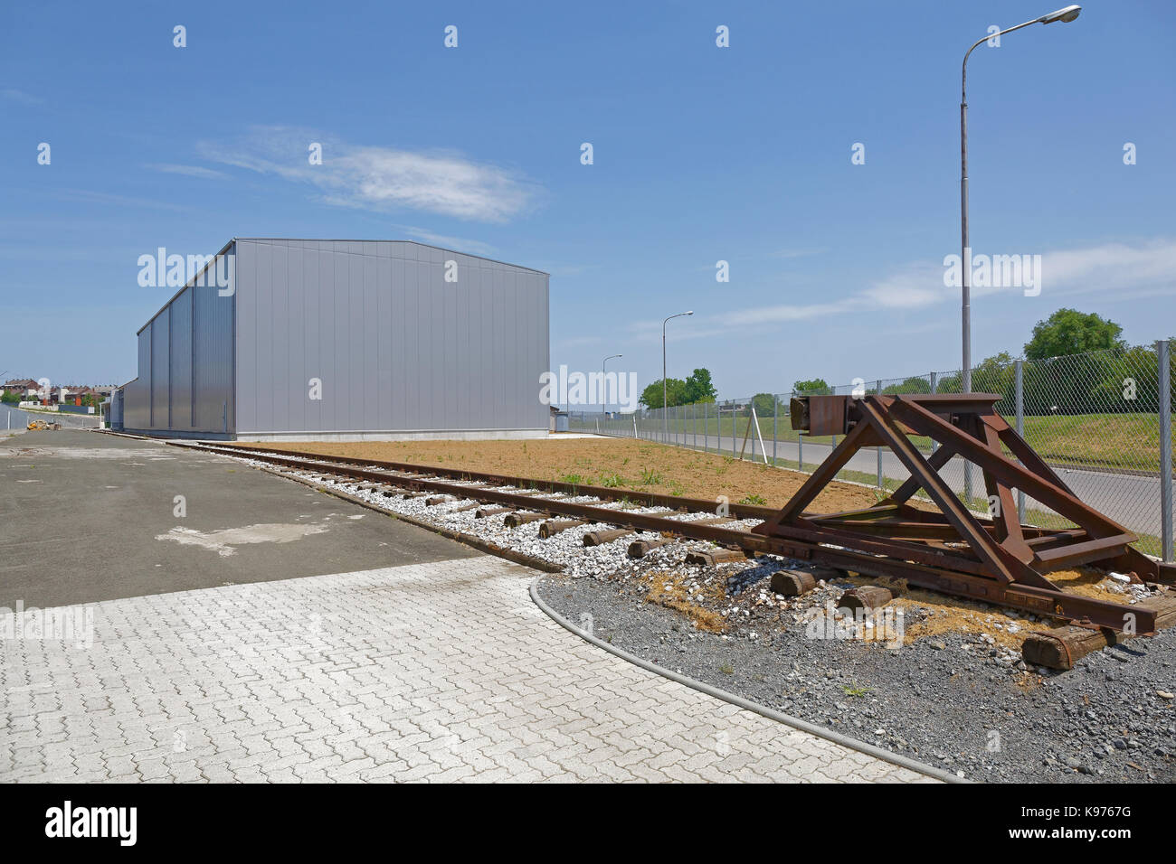 Distribution Warehouse Building With Railroad Tracks - Stock Image