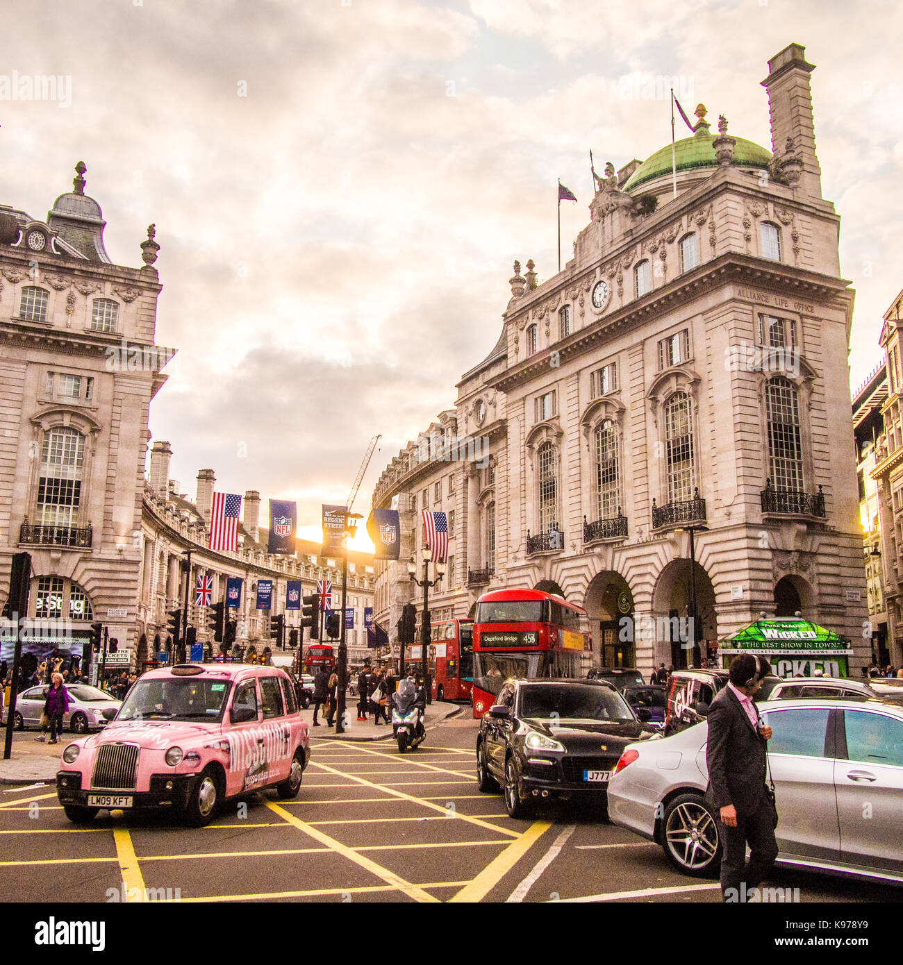 Pink Taxi navigates around Picadilly Circus with Regent Street behind Stock Photo