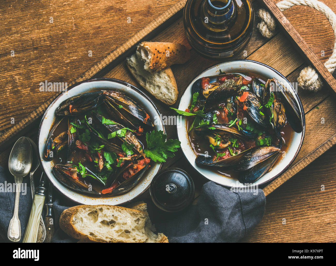 Belgian boiled mussels in tomato sauce with parsley, copy space - Stock Image