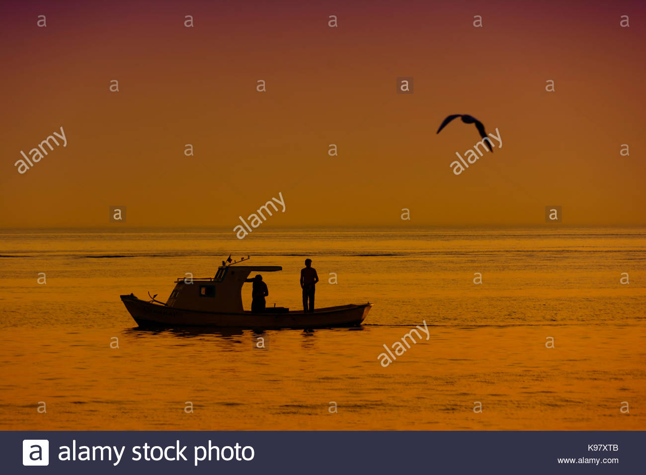 fisherman and boat on sea with seagull sillhouette landscape photography - Stock Image
