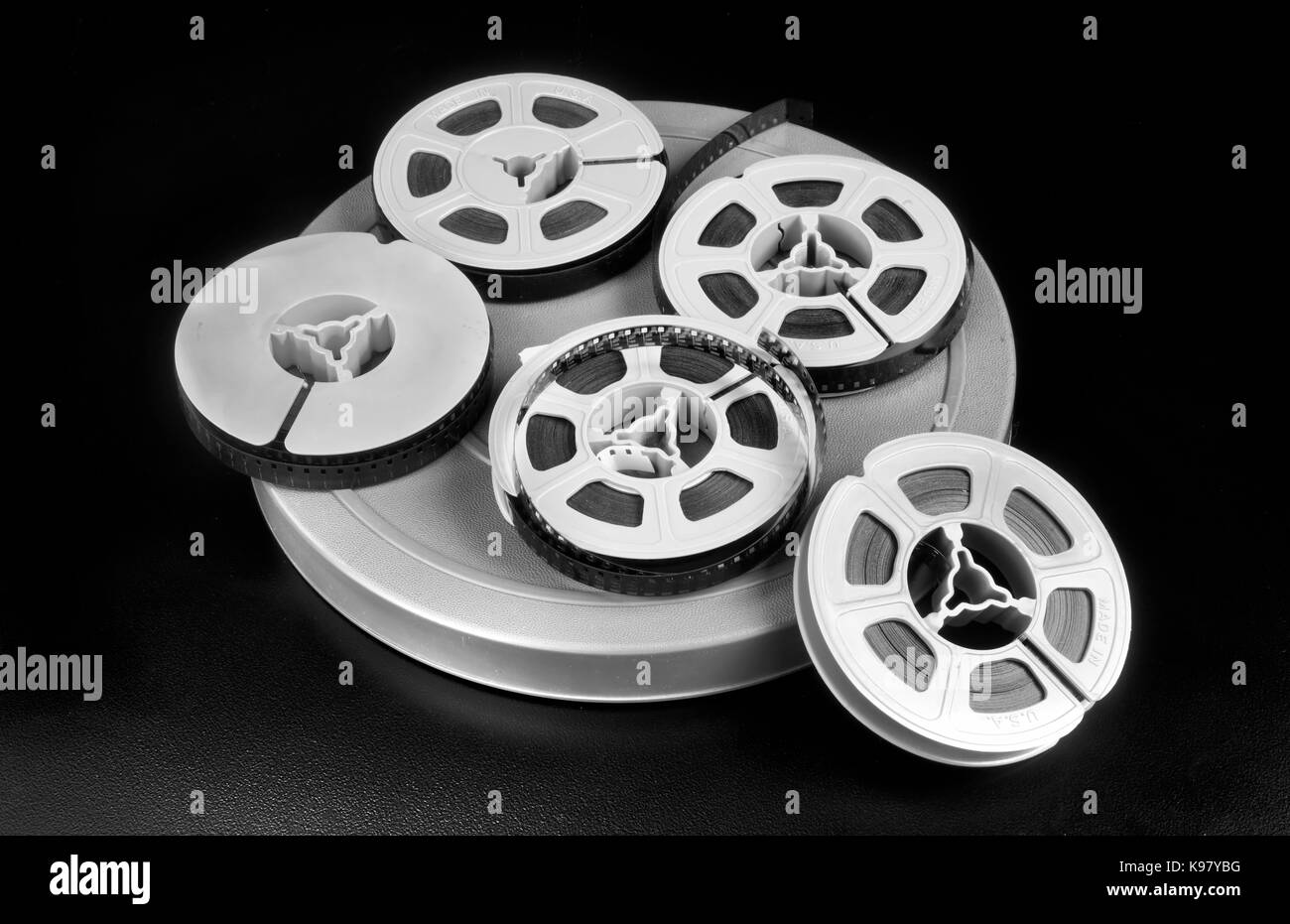 Old time 8mm film and film canisters in black and white. - Stock Image