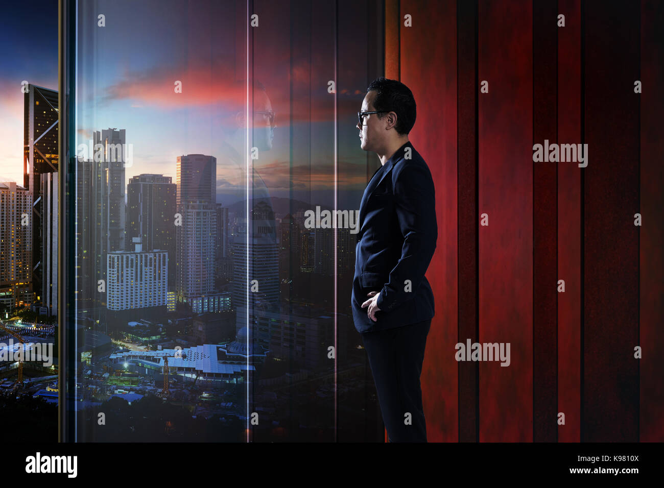 Young businessman looking out the city in the office . evening scene. . - Stock Image