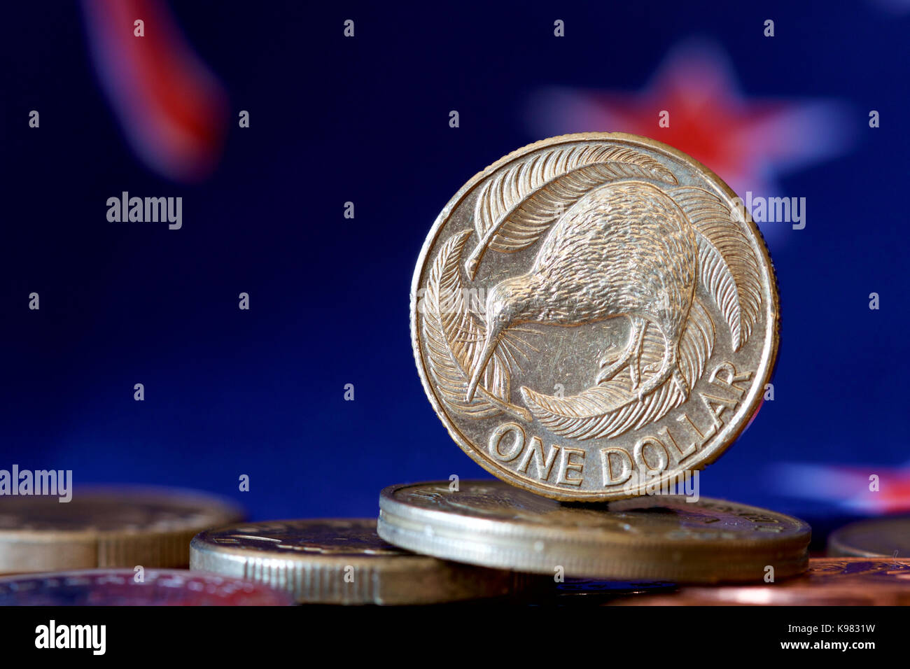 NZ one dollar coin with background of national flag. - Stock Image
