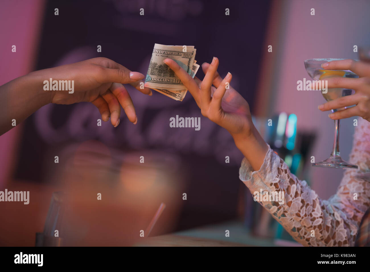 woman paying barman for cocktails - Stock Image