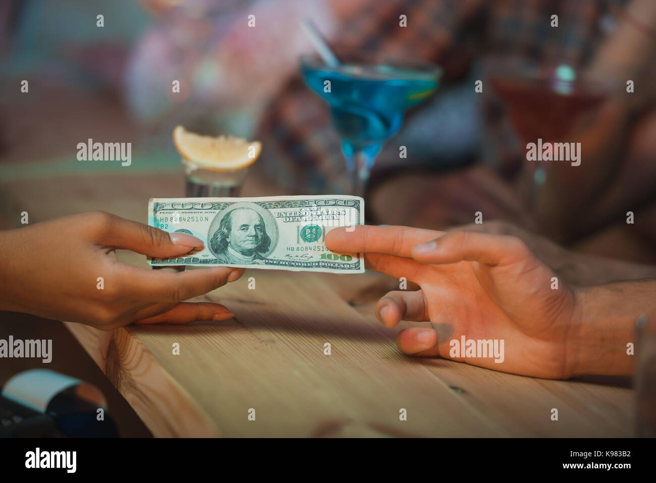 man paying barman for cocktails - Stock Image