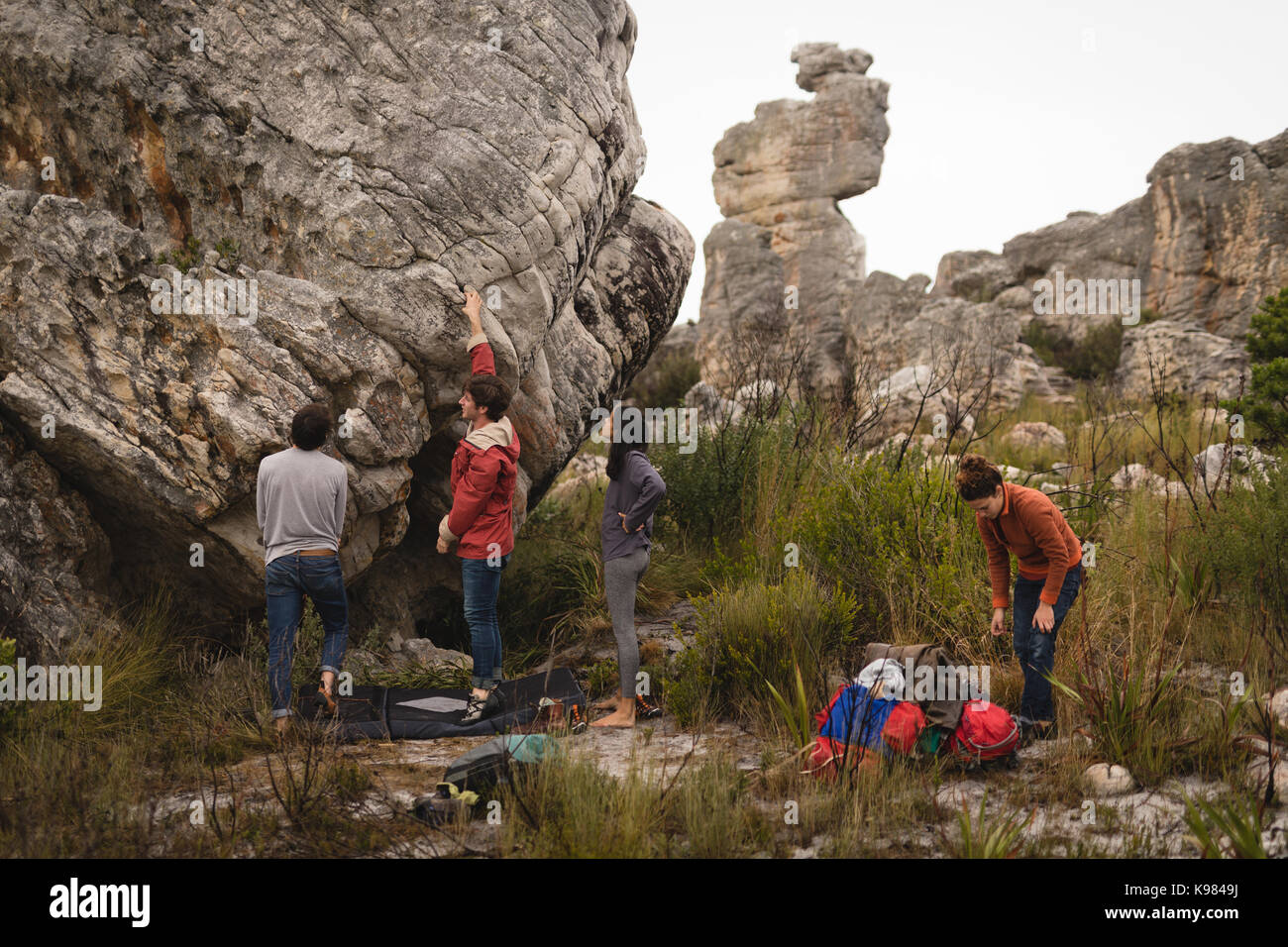 Friends examining cliff during mountaineering - Stock Image