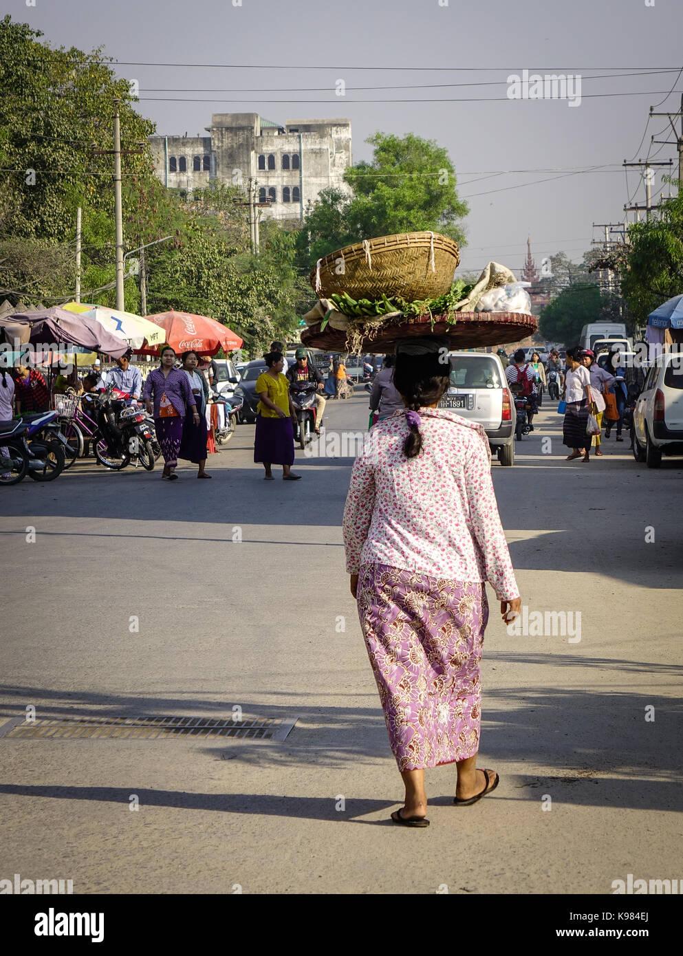 Yangon, Myanmar - Feb 11, 2017. A woman walking on sreet at sunny day in Yangon, Myanmar. Yangon boasts the largest - Stock Image