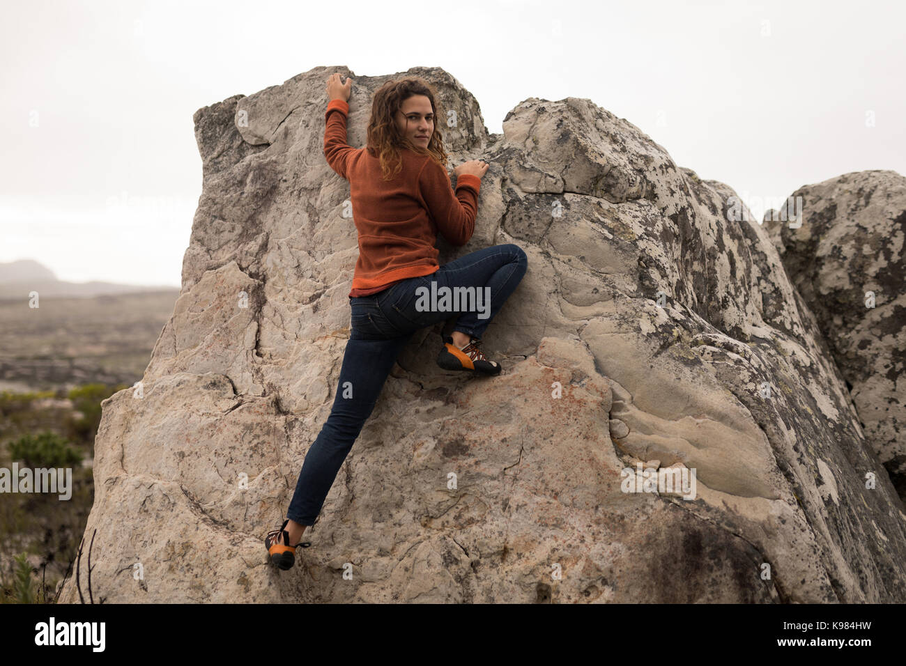 Portrait of confident woman climbing cliff on a sunny day - Stock Image