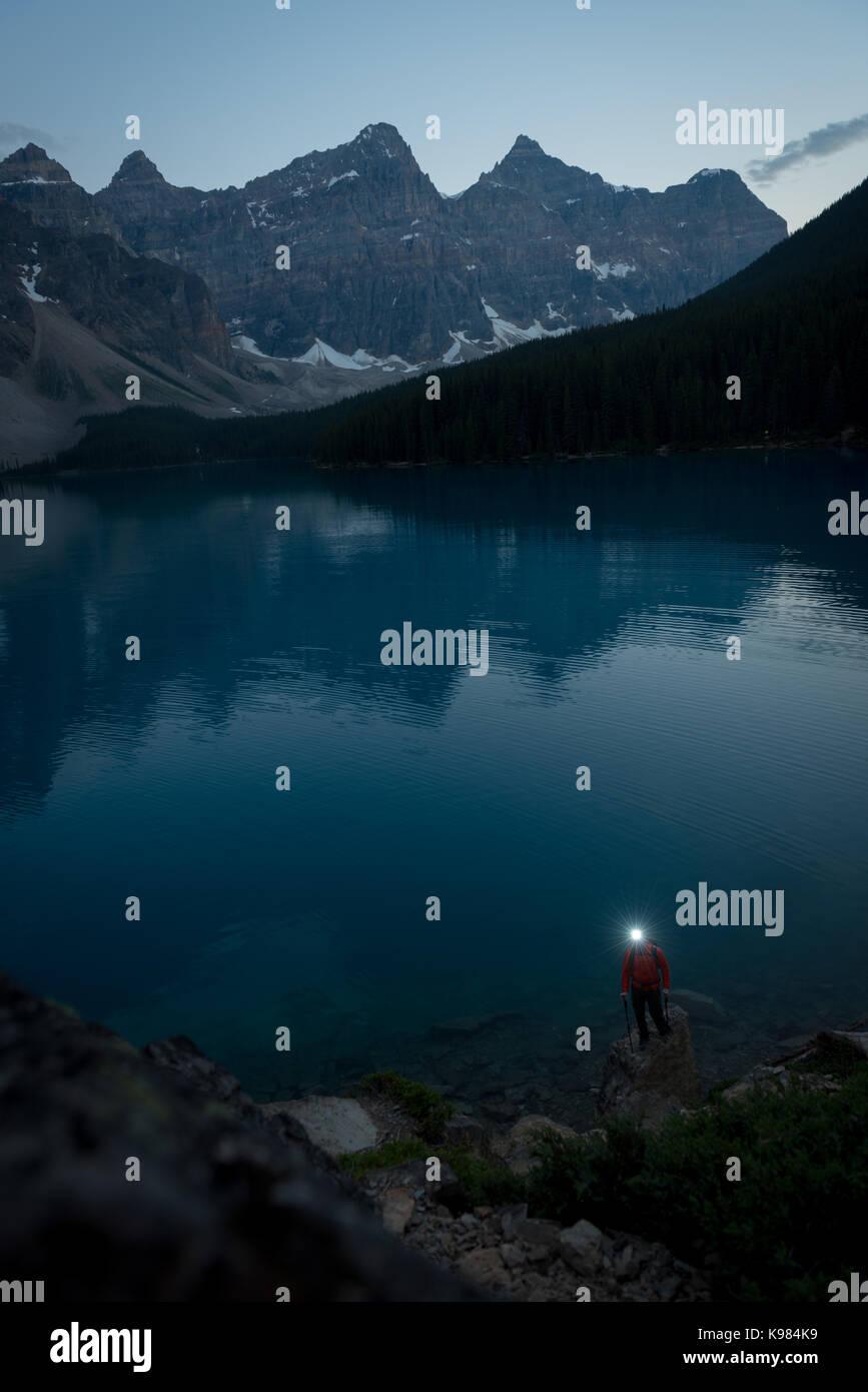 Hiker with headlamp walking near lake at night - Stock Image
