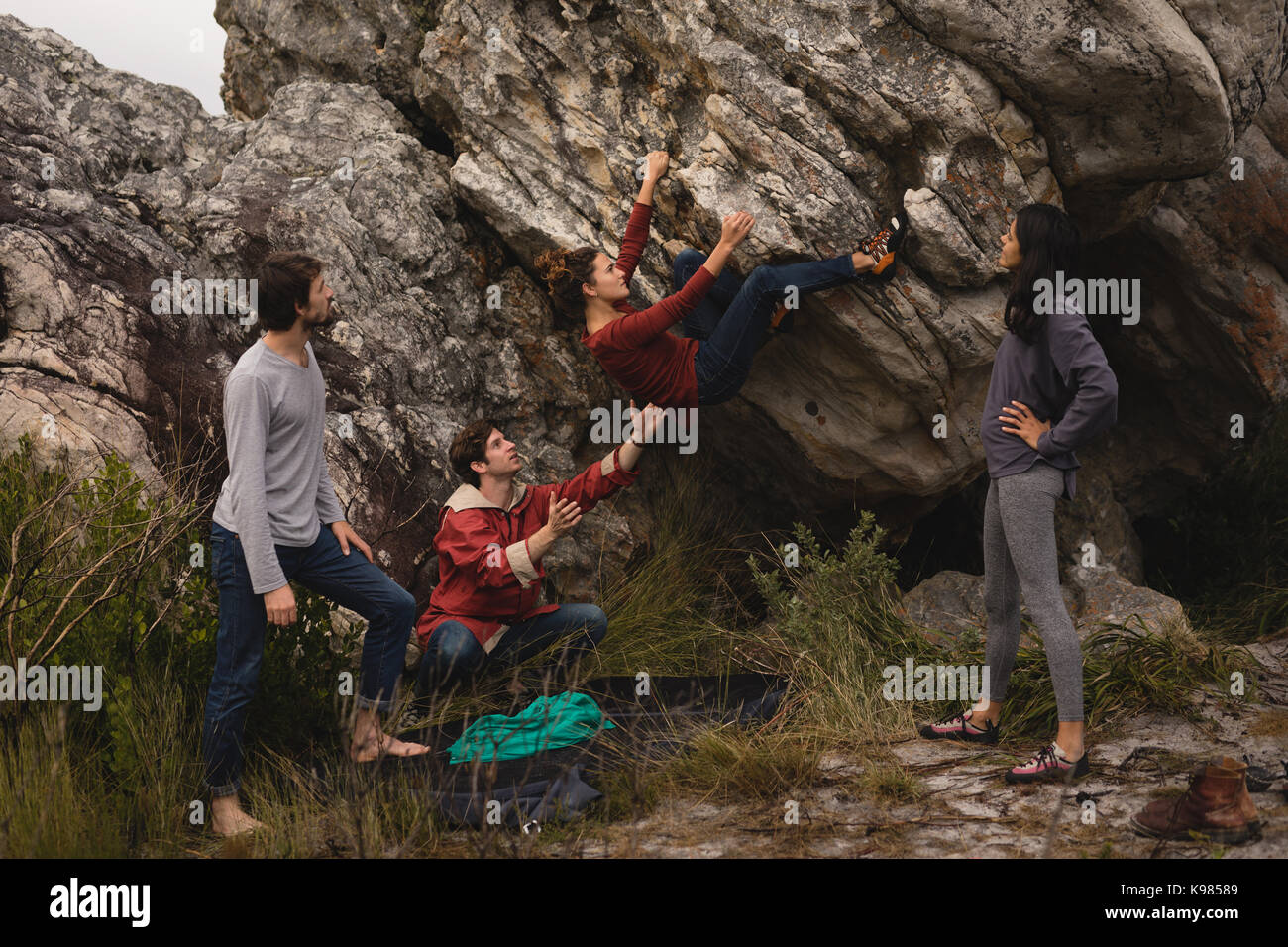 Friends assisting man in rock climbing on a sunny day - Stock Image