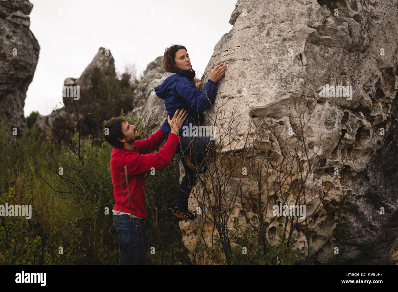 Man assisting woman in rock climbing on a sunny day - Stock Image