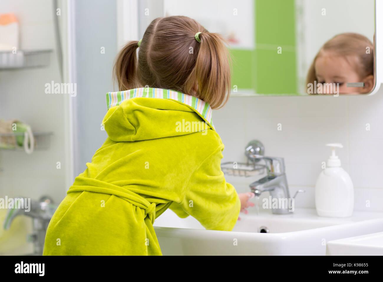 Little girl washing hands in bathroom - Stock Image