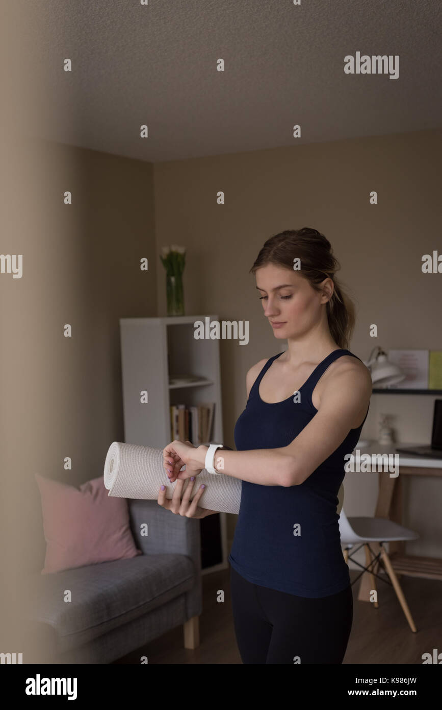 Young woman looking at smart watch while standing with exercise mat in living room at home - Stock Image