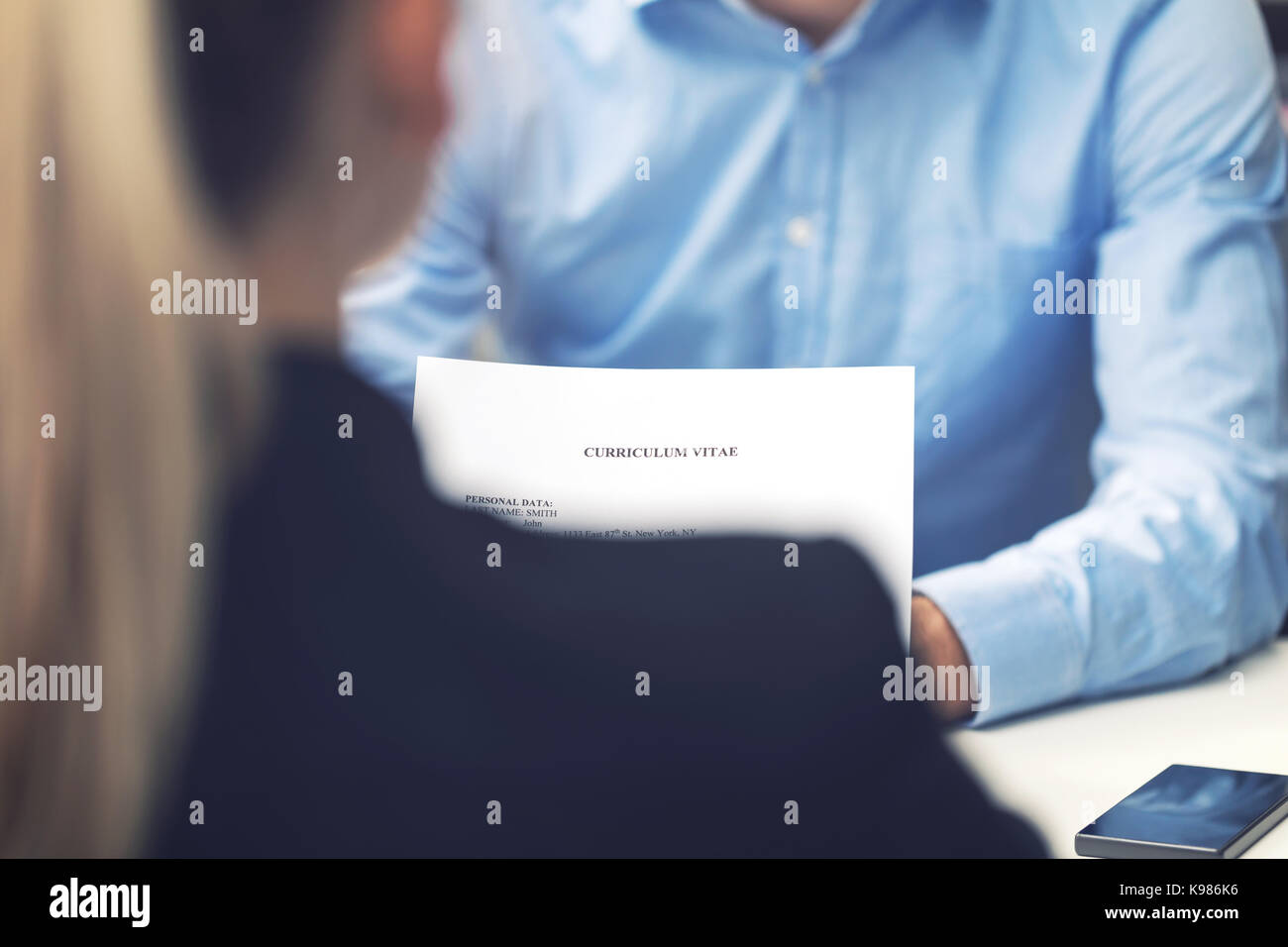 job interview - business woman and candidate at office reading cv - Stock Image