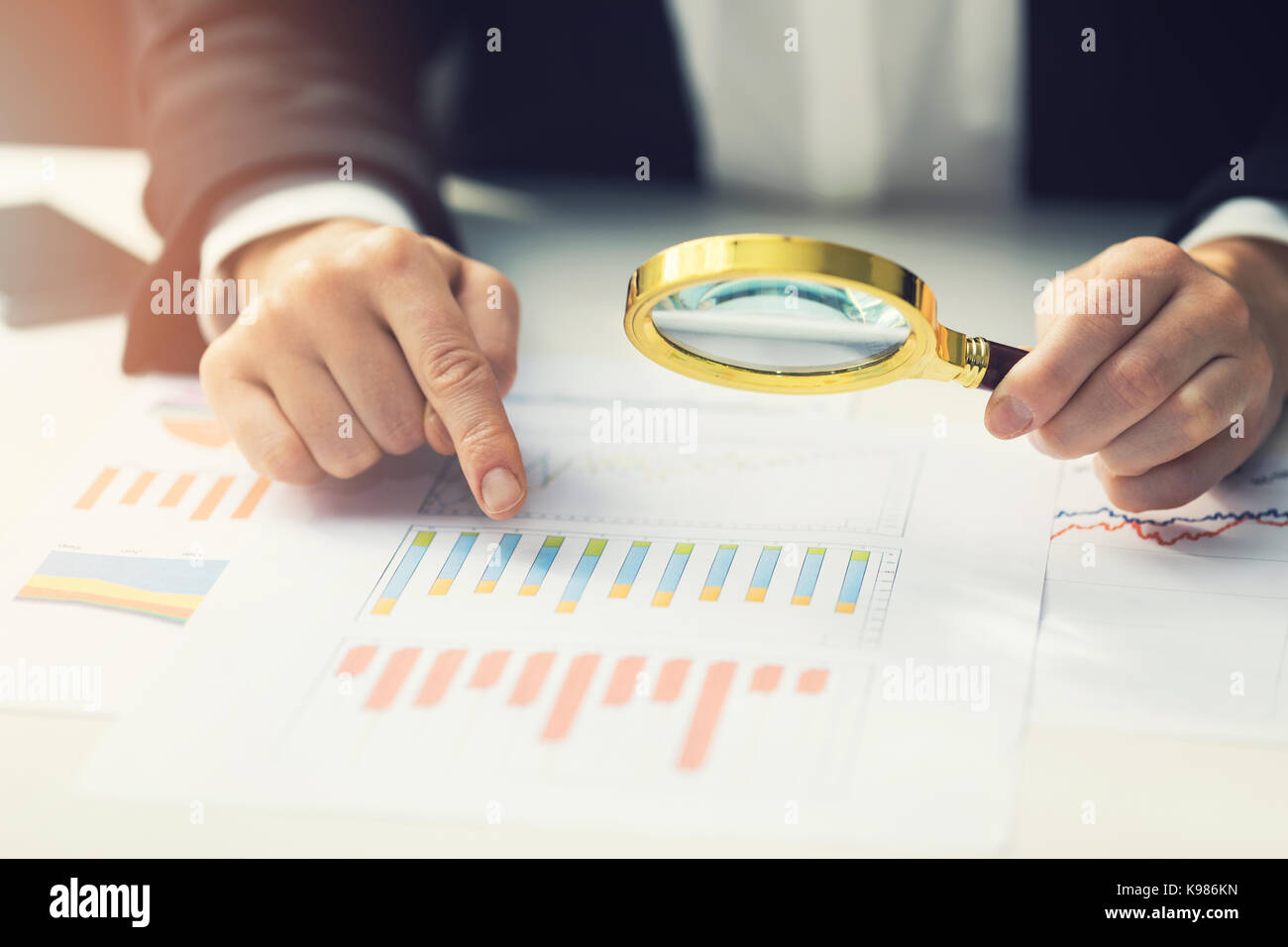 business women using magnifying glass to review financial summary chart report. auditing concept - Stock Image