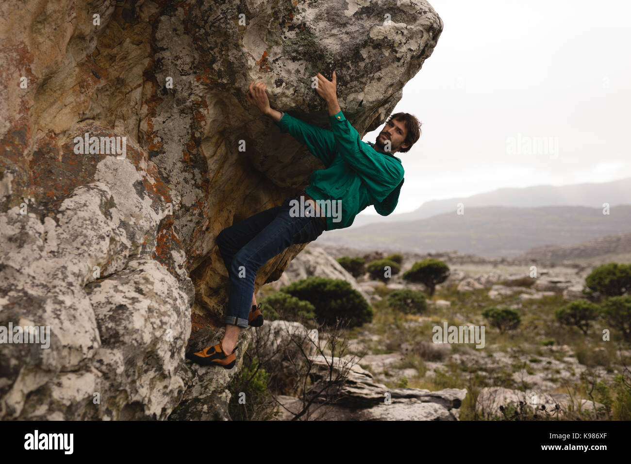 Man climbing mountain on a sunny day - Stock Image