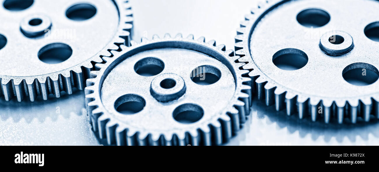 Two large and a small gear wheel which overlap. - Stock Image