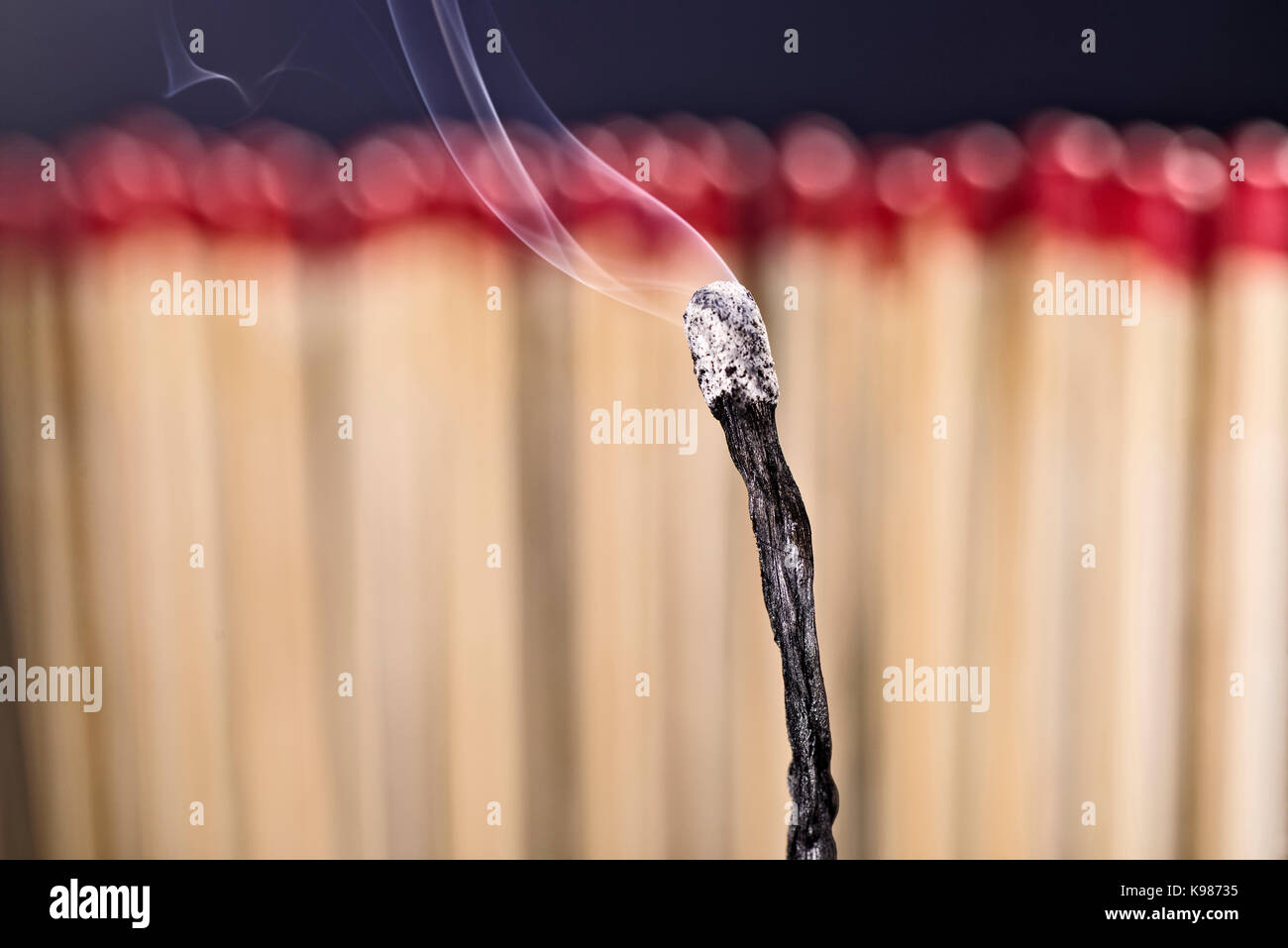 Burned matchstick in front of a new set of matches - Stock Image