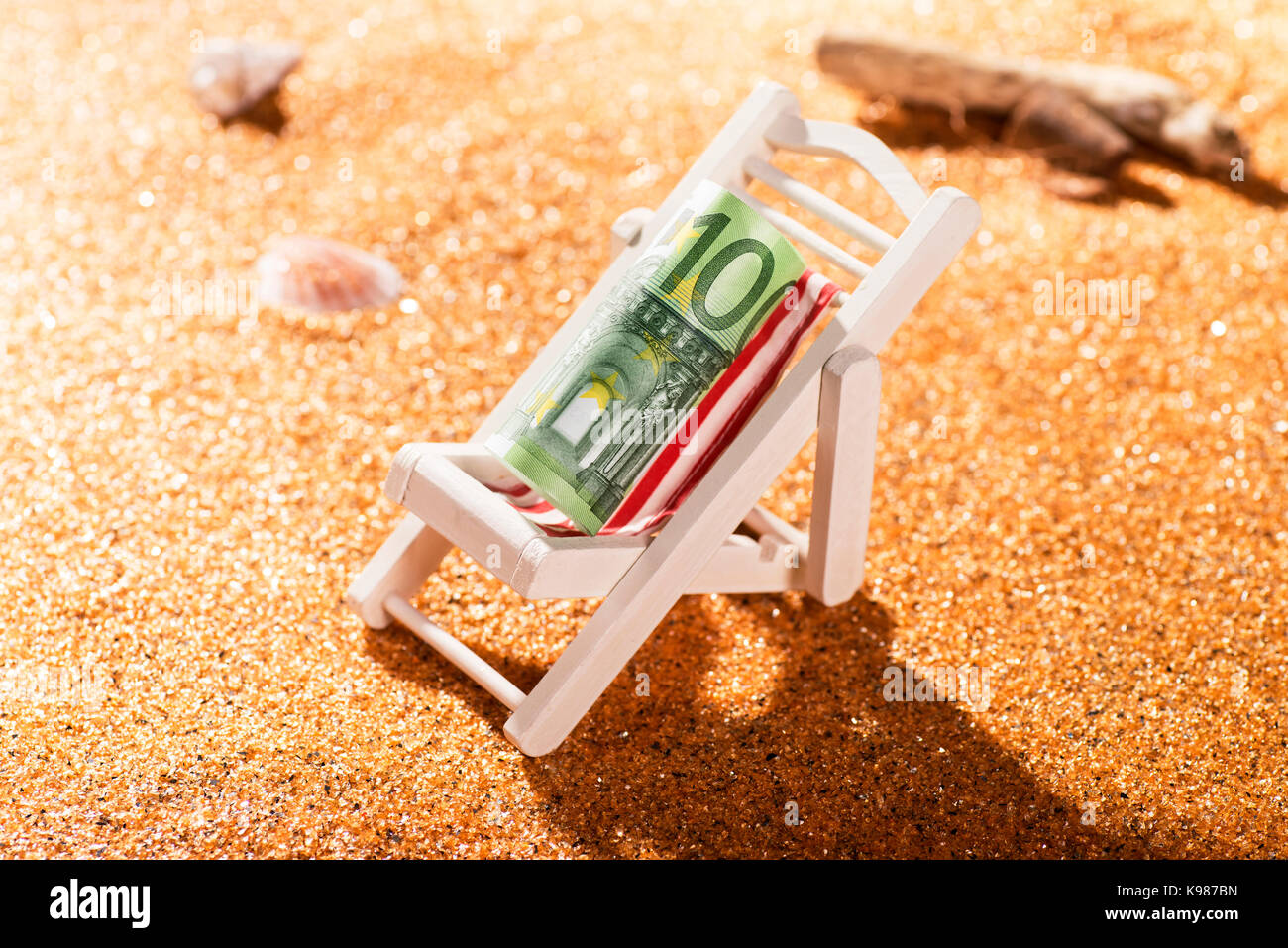 A rolled 100 euro banknote on a deck chair in a beach scene - Stock Image