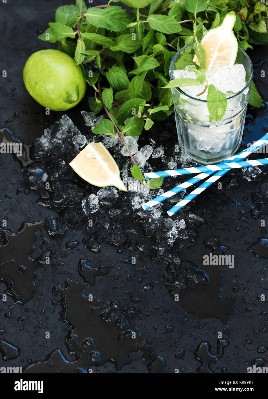 Mojito cooking set. Bunch of fresh mint, lime, chipped ice and coctail glass over black slate stone backdrop - Stock Image