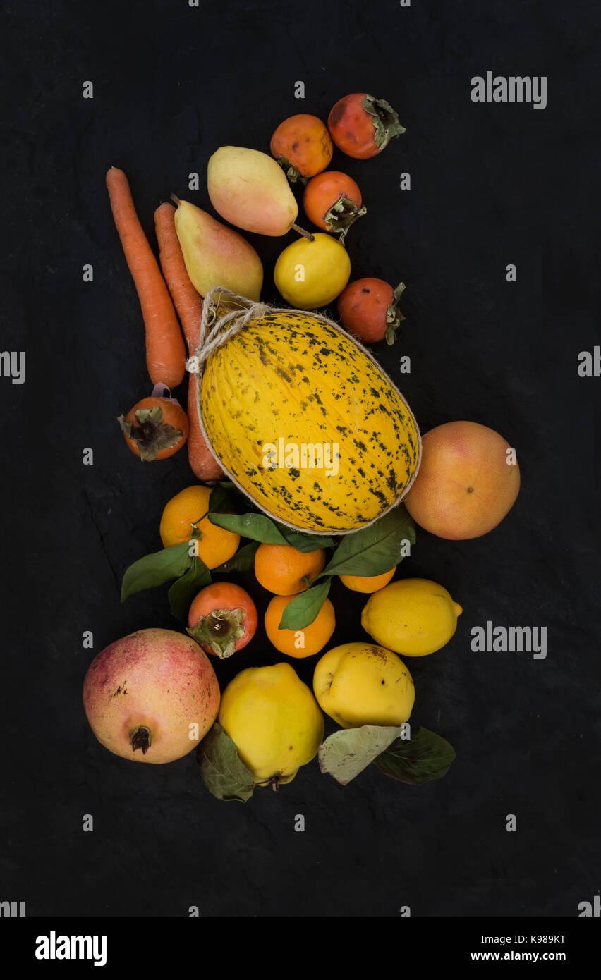 Mixed yellow orange fruit and veggies assortment, ingredients for smoothie. Melon, garnet, grapefruit, carrot, persimmon, - Stock Image