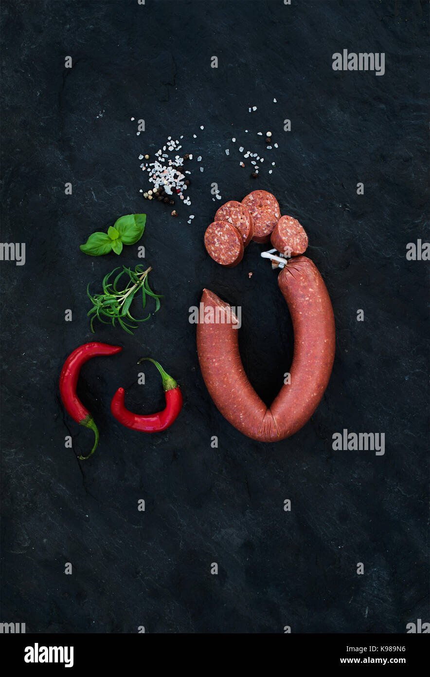 Smoked salami sausage with rosemary, chili pepper, basil and salt over black slate stone background, top view. - Stock Image