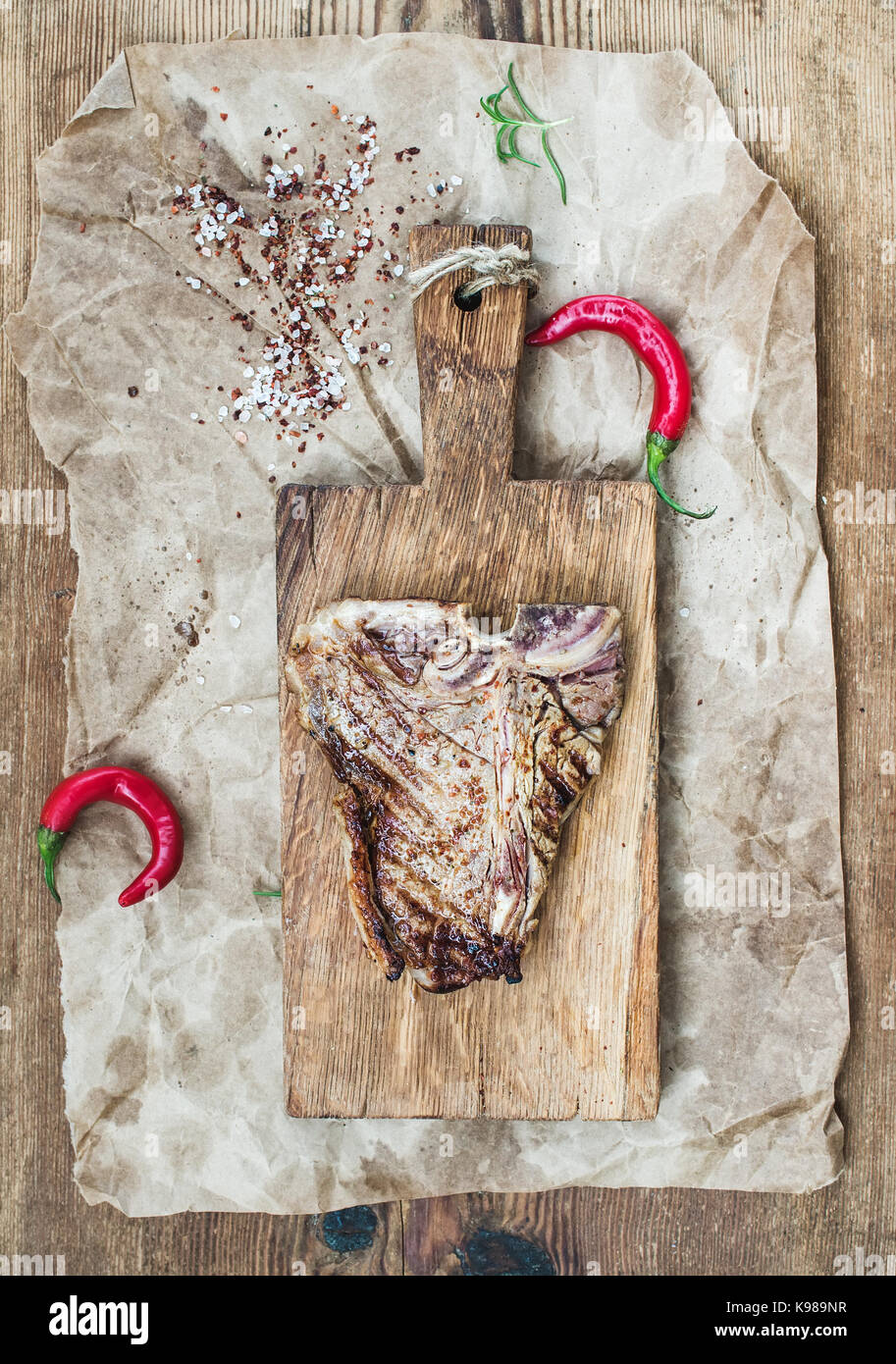 Cooked meat t-bone steak on serving board with red chili peppers, spices, fresh rosemary over oily craft paper and Stock Photo