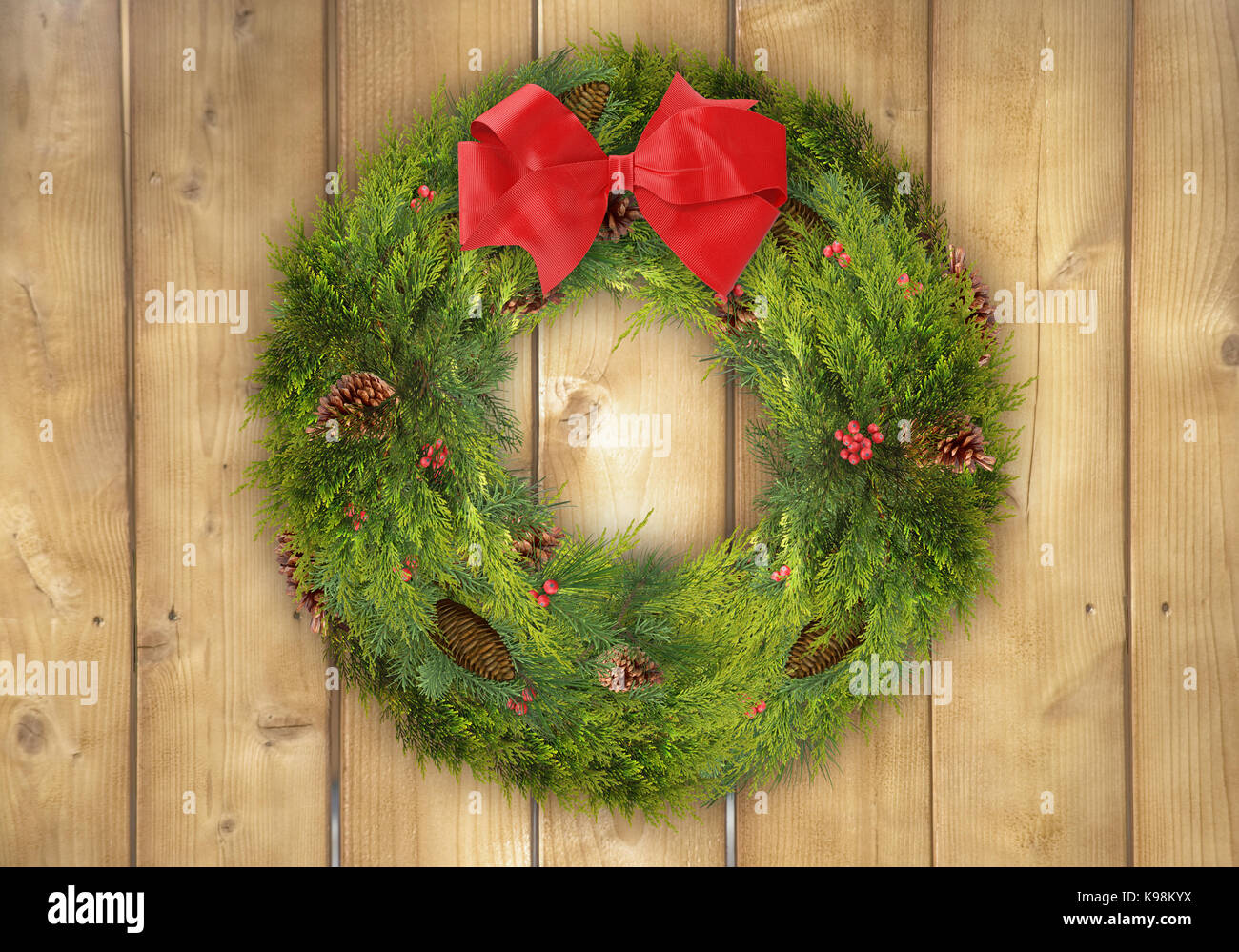 Rustic Christmas Background Of A Pine Wreath With Holly Berries And Big Red Bow On Wood Fence