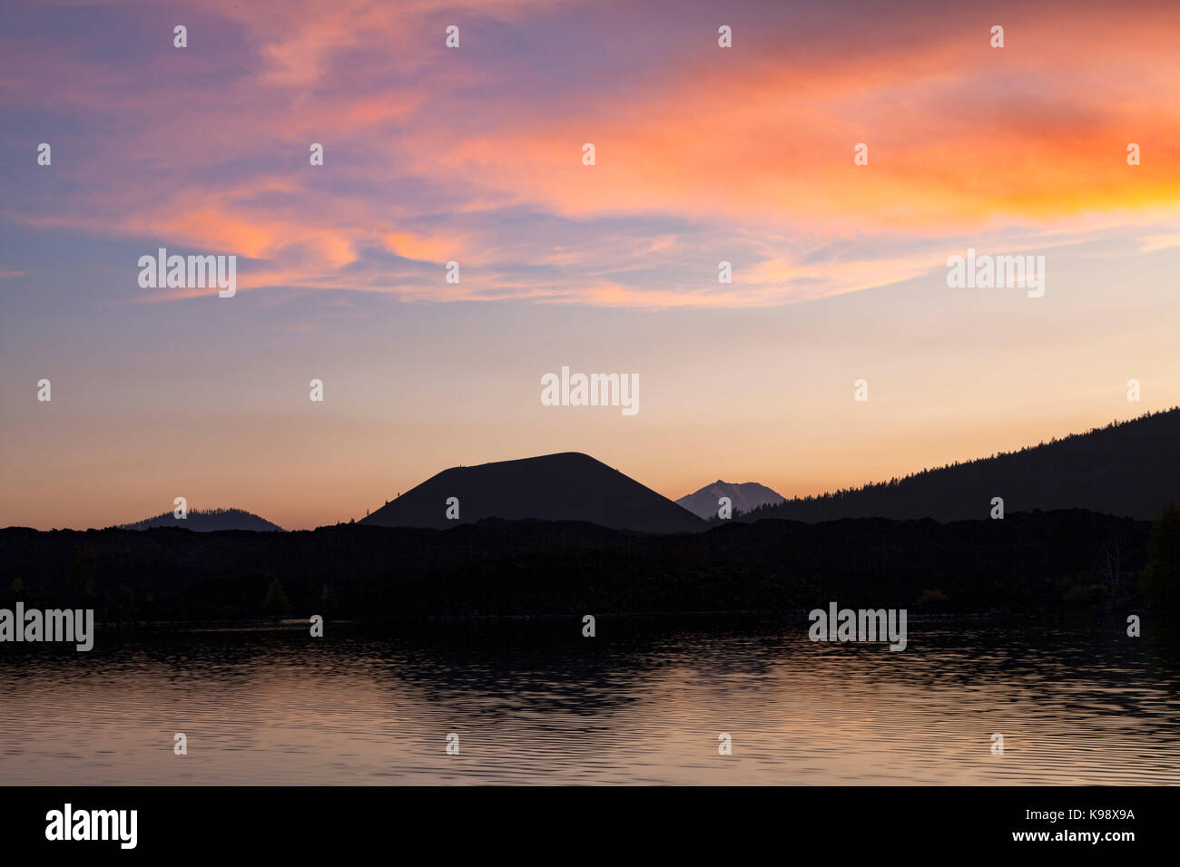 Fairfiield Peak, Cinder Cone, and Mt. Lassen are silhoutted by a sunset sky in Lassen Volcanic National Park. Fairfield - Stock Image